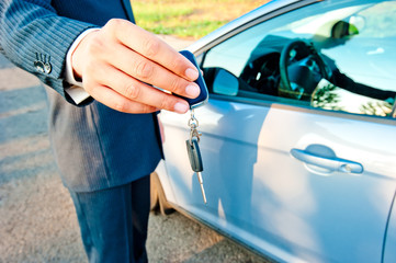 man-manager transmits the key to the new car buyer