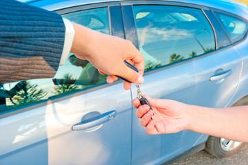 handing the keys to a new car customer