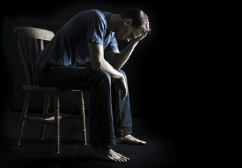 depressed or sad man sitting on chair in the dark