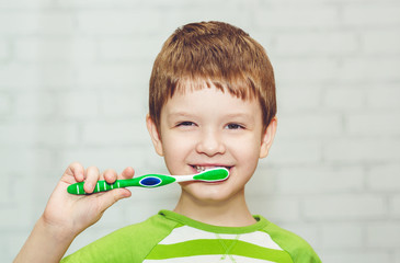 Portrait of the little boy brushing hes teeth