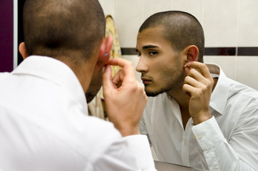 Handsome young man looking at ear piercing
