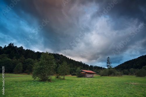 stormy sunset over alpine meadows
