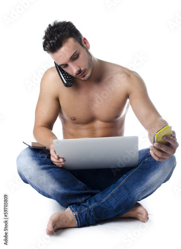 Shirtless young man overwhelmed by technology