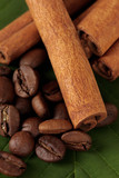 Coffee grains and cinnamon on sackcloth on green leafs close-up
