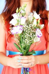 Woman holding bouquet, on blue background, close-up