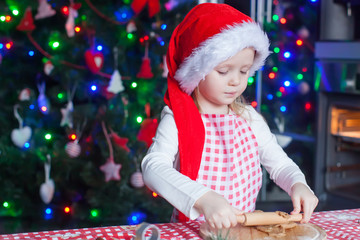 Little girl with rolling pin baking Christmas gingerbread