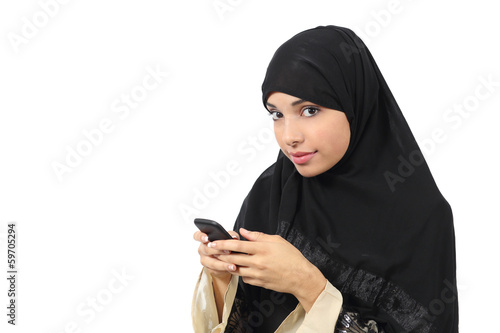 Arab woman browsing a smart phone and looking to the camera