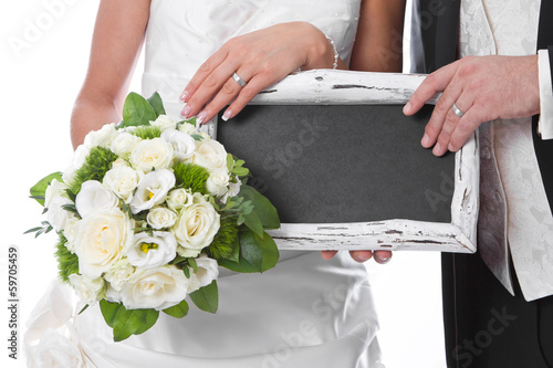 Fresh married couple holding a sign for advertising in her hands