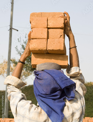 Female worker carry brick on her head