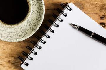 work desk with paper, pen and cup of instant coffee