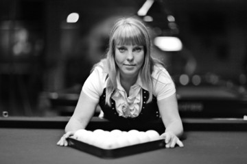 beautiful blonde aims in the course of game at billiards