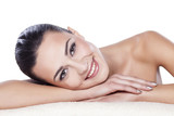 Fototapety portrait of a beautiful girl lying on a towel on a white