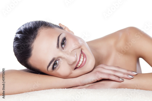 portrait of a beautiful girl lying on a towel on a white