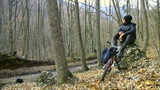 Teen on bike is resting in the autumn forest