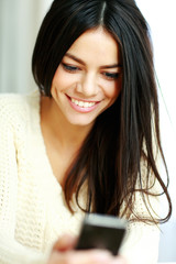 Closeup portrait of a cheerful young woman using her smartphone