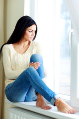 Young beautiful woman sitting on a window-sill