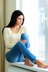 Young thoughtful woman sitting on a window-sill