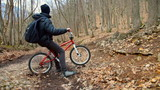 Teen boy rides a bicycle in the autumn forest