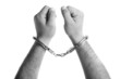 closeup of the hands of a man with handcuffs in black and white