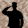 Saluting soldier's silhouette on a desert army camouflage backgr