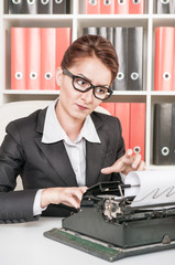Mature business woman working with typewriter