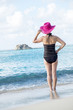 Woman in Pink Straw Hat Standing on a Caribbean Beach