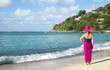 Woman in Pink Hat and Wrap Standing on a Caribbean Beach