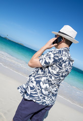 Man Talking on His Smart Phone on a Caribbean Beach