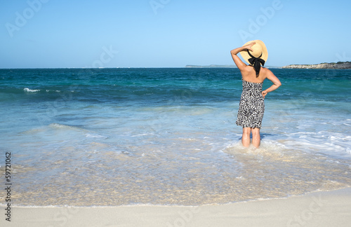 Woman in Sundress and Straw Hat Standing in the Ocean