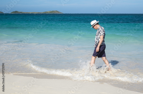 Man Walking on a Caribbean Beach Looking Down