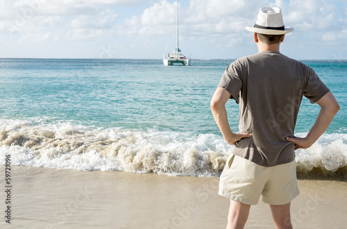 Back View of a Man on a Beach Looking at a Catamaran