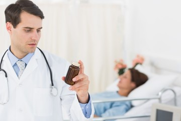 Doctor holding a bottle of pills with patient in hospital