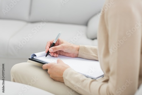 Mid section of a financial adviser writing notes