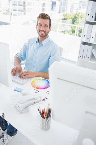 Smiling male photo editor using computer