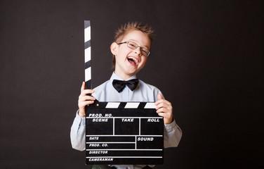 Little boy holding clapper board in hands.