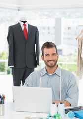 Smiling male fashion designer using laptop in the studio