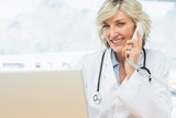Smiling female doctor using laptop and phone