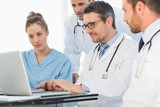 Group of concentrated doctors using laptop