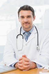 Male doctor with laptop at desk in medical office
