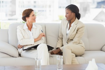 Happy businesswomen planning in diary together on the sofa