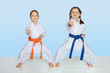Little cheerful athletes in kimono beat punch hand