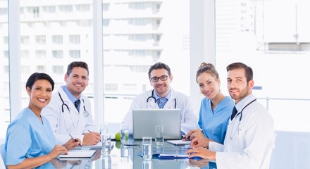 Smiling medical team around desk in office