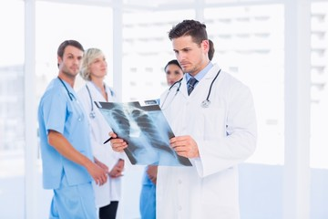 Doctor examining x-ray with colleagues standing behind