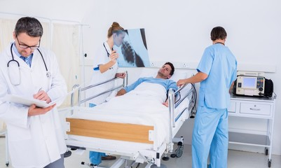 Doctors holding reports by patient in at hospital