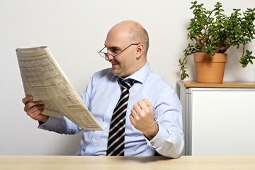 Geschäftsmann liest eine Zeitung in seinem Büro und jubelt