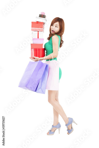 surprised young woman holding gift box and shopping bag