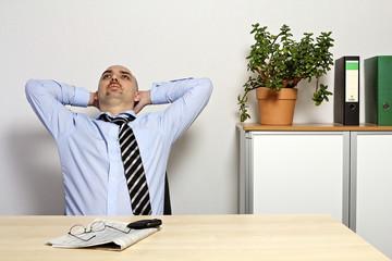 Geschäftsmann sitzt in seinem Büro und träumt