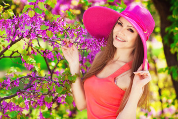 portrait of a beautiful young woman in a bright summer hat