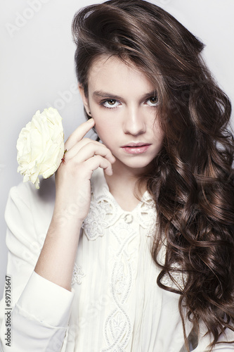 Beautiful portrait of young girl with curly hair and white rose