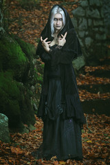 Dark witch posing in the woods